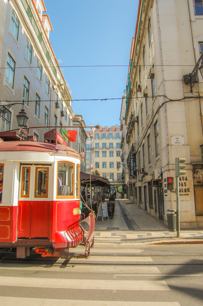 Walking in Lisbon with red tram